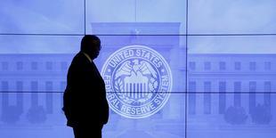 Охранник на фоне изображения здания ФРС США и логотипа регулятора в Вашингтоне 16 марта 2016 года. Представители Федрезерва США посчитали, что американская экономика может быть готова к новому повышению процентных ставок в июне, следует из протокола апрельского заседания центробанка, опубликованного в среду. REUTERS/Kevin Lamarque/File Photo
