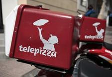 Telepizza dijo el jueves que ha alcanzado un acuerdo con un socio franquiciado para iniciar la apertura de esteblecimientos en Reino Unido, donde prevé alcanzar unas 300 tiendas en una década. En la imagen, logos de Telepizza en motos de reparto junto a un restaurante en Madrid, el 5 de abril de 2016. REUTERS/Andrea Comas