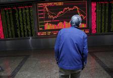 Un inversor mira un tablero electrónico que muestra la información de las acciones, en una correduría en Pekín, China, 15 de febrero de 2016. Las acciones chinas cedieron levemente el jueves, y el volumen de operaciones cayó a mínimos en casi tres meses y medio luego de que muchos inversores se abstuvieron de participar por las preocupaciones económicas y el temor a que las tasas de interés de Estados Unidos suban pronto. REUTERS/Kim Kyung-Hoon
