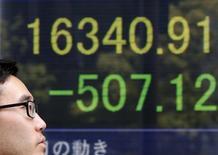 Un hombre camina frente a un tablero electrónico que muestra el índice Nikkei, afuera de una correduría en Tokio, Japón. 18 de abril de 2016. El índice Nikkei de la bolsa de Tokio cerró con pocos cambios el jueves, moviéndose dentro y fuera de territorio positivo luego de que la cautela general contrarrestó algunas ganancias por la publicación de las minutas de la Reserva Federal de Estados Unidos. REUTERS/Toru Hanai