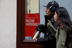 "People walk past a ""Now Hiring"" sign in Manhattan in New York City, U.S., May 10, 2016.  REUTERS/Brendan McDermid"
