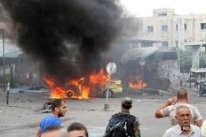 Сирийский военнослужащий и гражданские осматривают место взрыва в Тартусе 23 мая 2016 года. Взрывы в сирийских прибрежных городах Джабле и Тартусе, подконтрольном правительству районе размещения российских сил, унесли более 100 жизней в понедельник, сообщили правозащитники. SANA/Handout via REUTERS