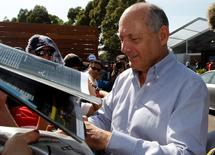 Chairman and CEO of McLaren Formula One team Ron Dennis signs autographs at the first practice session of the Australian F1 Grand Prix at the Albert Park circuit in Melbourne March 14, 2014. REUTERS/Brandon Malone