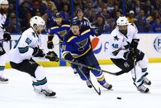 May 23, 2016; St. Louis, MO, USA; San Jose Sharks right wing Joel Ward (42) and St. Louis Blues right wing Vladimir Tarasenko (91) chase the puck in game five of the Western Conference Final of the 2016 Stanley Cup Playoffs at Scottrade Center. Mandatory Credit: Billy Hurst-USA TODAY Sports