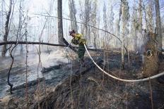 FILE PHOTO - A member of Wildfire Management Alberta's Wild Mountain Unit out of Hinton, hoses down hotspots in the Parsons Creek area of Fort McMurray, Alberta, Canada, May 6, 2016.  Chris Schwarz/Government of Alberta/Handout/File Photo via REUTERS