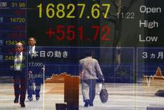 Люди отражаются в экране, демонстрирующем котировки индекса Nikkei, в Токио 19 апреля 2016 года. Японский фондовый рынок вырос до максимума почти одного месяца по итогам торгов среды, поскольку укрепление доллара после выхода сильной статистики о продажах нового жилья в США оказало поддержку акциям экспортёров, а бумаги Sony Corp взлетели после публикации финансовой отчётности компании. REUTERS/Thomas Peter