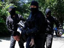 Полицейские ведут демонстранта, задержанного во время антиправительственной акции протеста в Алма-Ате. 21 мая 2016 года. Генеральная прокуратура Казахстана заявила, что правоохранительные органы расследуют ряд уголовных дел после прошедших 21 мая антиправительственных протестов в нескольких городах, и изучает вопрос финансирования уличных выступлений. REUTERS/Shamil Zhumatov