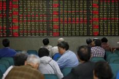 Inversores miran un tablero electrónico que muestra información bursátil, en una correduría en Shanghái, China. 21 de abril de 2016. Las acciones chinas subieron el lunes a pesar de que muchos inversores se abstuvieron de participar en el mercado por la incertidumbre sobre las perspectivas de la política monetaria de Pekín. REUTERS/Aly Song