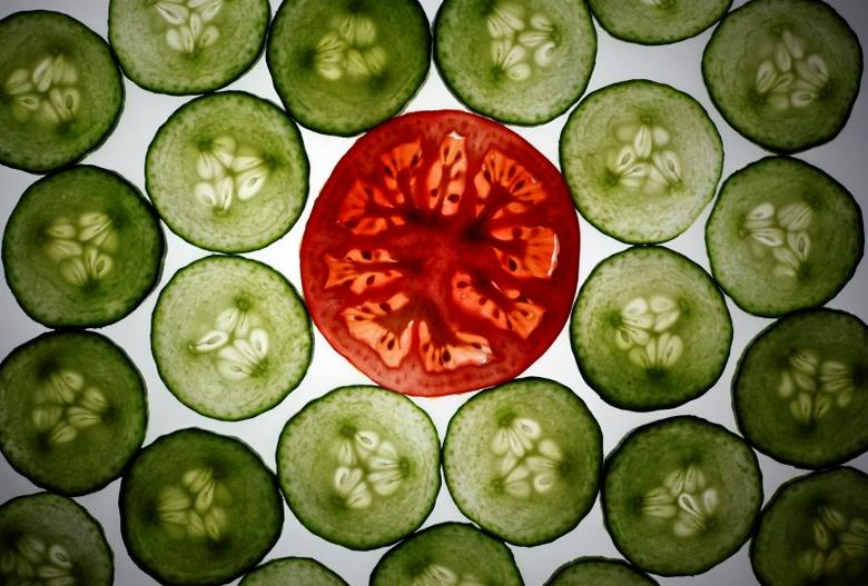 Slices of cucumber and a tomato slice are pictured in this illustration photo taken in Berlin May 30, 2011. REUTERS/Pawel Kopczynski