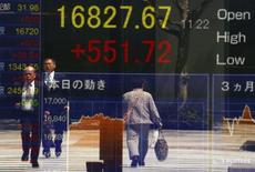 Люди отражаются в экране, показывающем котировки Nikkei average у биржи в Токио 19 апреля 2016 года. Японский фондовый рынок завершил торги вторника в плюсе пятую сессию кряду, поскольку растущие ожидания скорого повышения процентных ставок в США помогли доллару укрепить завоеванные ранее позиции по отношению к иене, что поддержало акции экспортных компаний. REUTERS/Thomas Peter