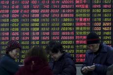 Инвесторы на фоне экрана, отображающего котировки, в брокерской конторе в Шанхае 15 февраля 2016 года. Китайский фондовый рынок продемонстрировал во вторник сильнейший однодневный рост, завершив торги на трехнедельных максимумах во главе с акциями финансового сектора, так как инвесторы ждут, что американский индексный провайдер MSCI Inc в следующем месяце впервые включит бумаги материкового Китая в индекс развивающихся рынков. REUTERS/Aly Song