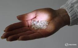 Сотрудница принадлежащей Алросе компании демонстрирует алмазы в Москве 18 октября 2013 года. Крупнейший в мире производитель алмазов в каратах - стоящая в очереди на приватизацию российская монополия Алроса, по итогам первого квартала 2016 года смогла улучшить финансовые показатели в годовом сравнении благодаря росту спроса на алмазы и бриллианты. REUTERS/Sergei Karpukhin