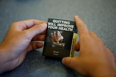 A high school student looks at a mock up of plain cigarette packaging before the start of a news conference in Ottawa, Ontario, Canada, May 31, 2016. REUTERS/Chris Wattie