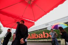 Personas caminan cerca de un cartel de Alibaba, en su campus en Hangzhou, China. 27 de mayo de 2016. SoftBank Group Corp anunció que venderá al menos 7.900 millones de dólares de sus acciones en la gigante minorista china Alibaba, una decisión del grupo japonés destinada a recortar deuda en medio de las preocupaciones generadas por las pérdidas de su filial estadounidense Sprint Corp. REUTERS/John Ruwitch
