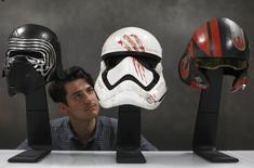 "A worker looks at replicas of Kylo Ren's helmet, Finn's Stormtrooper helmet and Poe Dameron's helmet from ""Star Wars: The Force Awakens"", in the Propshop headquarters at Pinewood Studios near London, Britain May 25, 2016.  REUTERS/Peter Nicholls"