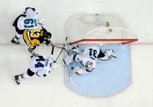 Pittsburgh Penguins left wing Conor Sheary (43) tries to get to the puck between San Jose Sharks defenseman Justin Braun (61) , defenseman Marc-Edouard Vlasic (44) and goalie Martin Jones (31) in game two of the 2016 Stanley Cup Final at Consol Energy Center.  Don Wright-USA TODAY Sports