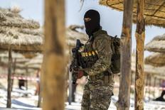 """Сотрудник спецслужб Туниса на пляже отеля Imperial Marhaba в Сусе 29 июня 2015 года. Ростуризм предупредил о угрозе нападений, исходящей от связанных с ультраджихадистами """"Исламского государства"""" группировок, в Тунисе, традиционно популярном направлении отдыха для россиян, в высокий туристический сезон. REUTERS/Zohra Bensemra"""