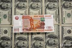 Рублевые и доалларовые купюры в Сараево 9 марта 2015 года.  Рубль начал торги четверга ростом на фоне очередного движения нефти Brent выше психологической отметки $50 за баррель и снижения негативного отношения мировых рынков к риску, утренняя динамика будет ограничена ожиданиями сегодняшних итогов заседаний ЕЦБ и ОПЕК, данных о нефтяных запасах в США, а также завтрашней публикации об американском рынке труда. REUTERS/Dado Ruvic