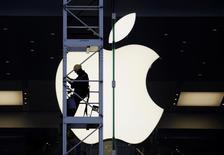 Wall Street abrió el jueves a la baja, afectado por las acciones de Apple y la caída de los títulos de las empresas de energía ante el descenso de los precios del petróleo. En la imagen, un trabajador sube a través de un andamio junto a un gran logo de Apple situado en la tienda de la compañía en Hong Kong, el 10 de abril de 2013.    REUTERS/Bobby Yip