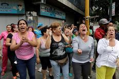 """Manifestantes gritan a miembros de la Guardia Nacional de Venezuela durante manifestaciones en Caracas. 2 de junio 2016. Las fuerzas de seguridad de Venezuela lanzaron el jueves gases lacrimógenos para detener el paso de cientos de manifestantes que protestaban por la escasez de alimentos al grito de """"queremos comida"""", a pocas cuadras del palacio presidencial. REUTERS/Marco Bello"""