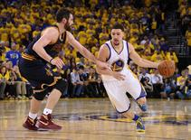 Golden State Warriors guard Klay Thompson (11) moves the ball against Cleveland Cavaliers forward Kevin Love (0) during the second half in game one of the NBA Finals at Oracle Arena. Mandatory Credit: Kyle Terada-USA TODAY Sports