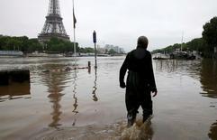 Homem andando em rua alagada ao lado da torre Eiffel, em Paris.    02/06/2016        REUTERS/Pascal Rossignol