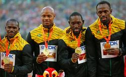 Usain Bolt of Jamaica (R) and teammates Nesta Carter, Asafa Powell, Nickel Ashmeade, gold medallists, pose on the podium after the men's 4 x 100 metres relay event during the 15th IAAF World Championships at the National Stadium in Beijing, China, August 30, 2015. REUTERS/Damir Sagolj