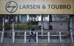 A man waits at a bus-stop with an advertisement of Larsen & Toubro outside the company's manufacturing unit in Mumbai January 22, 2014. REUTERS/Danish Siddiqui