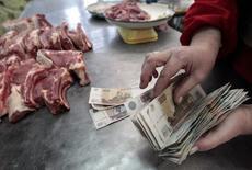 Торговец на ставропольском рынке держит деньги. 21 января 2016 года. Индекс потребительских цен в России в мае 2016 года составил 0,4 процента к предыдущему месяцу и 7,3 процента - к аналогичному периоду предыдущего года, сообщил Росстат. REUTERS/Eduard Korniyenko