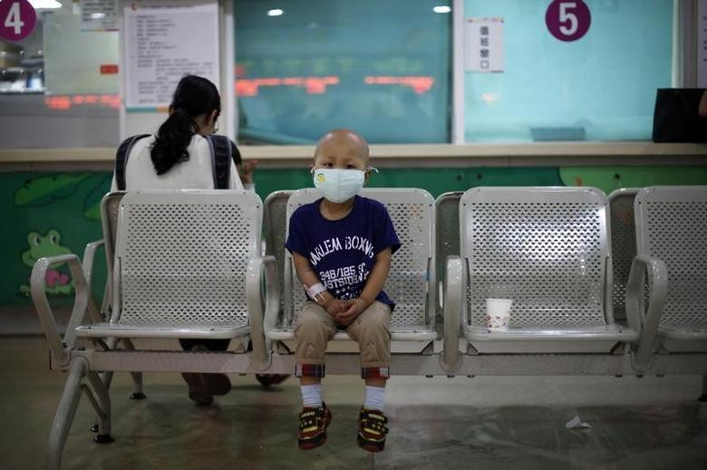 Four-year-old Niuniu, who has late-stage neuroblastoma, a malignant cancer of the nervous system, sits on a bench while his mother pays his medical bills after getting tested for his fifth round of chemotherapy at Shanghai Children's Hospital May 2, 2013. REUTERS/Aly Song