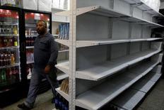 Человек шагает мимо пустых полок супермаркета в Каракасе 16 мая 2016 года. Жительница Венесуэлы была застрелена в понедельник при нападении мародёров на государственные продовольственные склады в объятой кризисом стране, пострадавшей от дешевизны нефти. REUTERS/Marco Bello