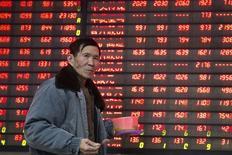Un inversor camina junto a un tablero electrónico que muestra información bursátil, en una correduría en Nanjing, China. 14 de enero de 2016. Las acciones chinas cerraron con escasa variación el martes, haciendo caso omiso a unas ganancias en Hong Kong y otros mercados asiáticos impulsadas por una disminución en las expectativas de alzas de las tasas de interés de Estados Unidos en el corto plazo. REUTERS/China Daily