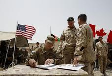 Канадский бригадный генерал Дин Милнер (в центре) стоит рядом с американским подполковником Стивом Миллером на базе Масум Гар Пенджави в провинции Кандагар, Афганистан, 5 июля 2011 года. США могут обратиться к Канаде за помощью в размещении новых сил НАТО в Восточной Европе, пока некоторые европейские союзники не торопятся выделять дополнительные подразделения для создания противовеса России, говорят дипломаты. REUTERS/Baz Ratner