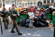 Soldiers pass by a pile of rubbish bags on the Grands boulevards in Paris, France, during a strike by garbage collectors and sewer workers of the city of Paris to protest the labour reforms law proposal, June 9, 2016.  REUTERS/Charles Platiau