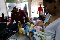 Una mujer compra alimentos básicos en una tienda en Caracas, Venezuela. 9 de junio de 2016. Venezuela está colocando a comités vecinales ligados al oficialista Partido Socialista Unido (PSUV) a cargo de la distribución de alimentos, en medio de crecientes y violentas protestas por una escasez crónica que ha golpeado la popularidad del presidente Nicolás Maduro. REUTERS/Ivan Alvarado