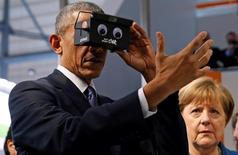 Президент США Барак Обама пробует очки виртуальной реальности, стоя рядом с канцлером Германии Ангелой Меркель в Гановере 25 апреля 2016 года. США и Германия в пятницу напомнили России, что болезненные санкции за роль в украинском кризисе могут быть отменены лишь при условии исполнения  Минских соглашений о деэскалации конфликта и заверили, что Запад заинтересован в партнерстве. REUTERS/Kevin Lamarque