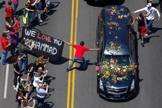 "A banner stating ""We Love You Mohammad"" is displayed as well-wishers touch the hearse carrying the body of the late boxing champion Muhammad Ali during his funeral procession through Louisville, Kentucky, U.S., June 10, 2016. REUTERS/Adrees Latif"