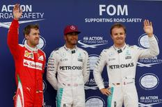 Formula One -Canadian Grand Prix - Montreal, Quebec, Canada - 11/06/16 - Ferrari F1 driver Sebastian Vettel (L), and Mercedes Benz F1 drivers Lewis Hamilton (C) and Nico Rosberg pose after qualifying session.  REUTERS/Chris Wattie
