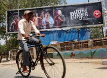 "A man rides his bicycle past a poster of the movie ""Udta Punjab"" in Mumbai, India, June 13, 2016. REUTERS/Shailesh Andrade"