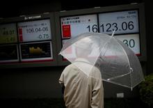 Un hombre mira una pantalla que muestra la tasa cambiaria entre el yen japonés, el dólar estadounidense y el índice Nikkei de Japón, afuera de una correduría en Tokio. La agencia Fitch Ratings dijo el lunes que podría rebajar la calificación de crédito soberano de Japón ante la preocupación por las reformas fiscales que lleva adelante el Gobierno, después de que el primer ministro Shinzo Abe aplazó una prevista alza del impuesto al valor agregado en dos años y medio. REUTERS/Issei Kato