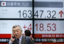 Мужчина проходит мимо экрана с котировками индекса Nikkei average у биржи в Токио 13, 2016. Японские акции выросли на волатильных торгах в среду, прервав четырёхдневные потери за счёт покрытия коротких позиций, в то время как приближающиеся итоги заседаний центральных банков и беспокойства о возможном выходе Великобритании из Евросоюза держат инвесторов в напряжении.  REUTERS/Toru Hanai