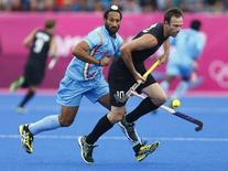 India's Sardar Singh (L) challenges New Zealand's Ryan Archibald during their men's Group B hockey match at the London 2012 Olympic Games at the Riverbank Arena on the Olympic Park August 1, 2012.        REUTERS/Dominic Ebenbichler