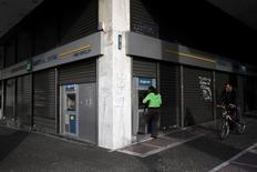 En la imagen de archivo, una mujer usa un cajero automático en una sucursal de un banco en Atenas. El Banco Central Europeo (BCE) casi con seguridad restablecerá la próxima semana el acceso de los bancos de Grecia a sus operaciones de financiación baratas, dijeron dos fuentes cercanas al asunto, lo que permitiría a los prestamistas griegos salir de una costosa línea de crédito de emergencia después de más de un año. REUTERS/Michalis Karagiannis