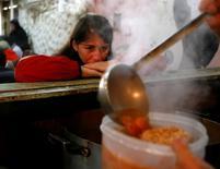 Una mujer espera un almuerzo gratuito en el comedor comunitario Bokitas en Buenos Aires. 10 de junio de 2016. La recuperación de la economía argentina prometida por el presidente Mauricio Macri para la segunda mitad del año parece tan improbable que se ha convertido en el blanco de chistes en Twitter. REUTERS/Enrique Marcarian