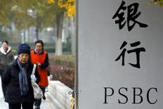 Люди идут мимо отделения Postal Savings Bank of China в Пекине. Китайский Postal Savings Bank, крупнейший национальный кредитор по количеству отделений, может на следующей неделе подать заявку на проведение первоначального размещения акций в Гонконге стоимостью до $8 миллиардов, сообщили люди, близкие к сделке. REUTERS/Kim Kyung-Hoon/File Photo