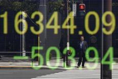 Una persona se refleja en una pantalla que muestra el índice Nikkei de Japón, afuera de una correduría en Tokio, Japón. 18 de abril de 2016. El índice Nikkei de la bolsa de Tokio subió el viernes, rebotando desde los mínimos en cuatro meses que anotó en la sesión previa, luego de que el yen se estabilizó. REUTERS/Toru Hanai