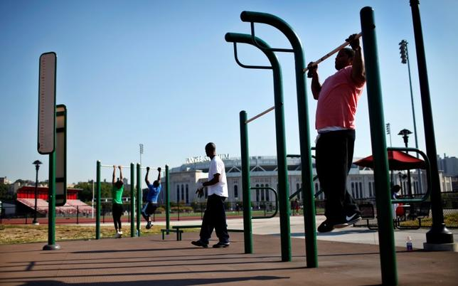 People work out in an outdoor exercise area at Macombs Dam Park in the Bronx section of New York City, September 13, 2012.  REUTERS/Mike Segar
