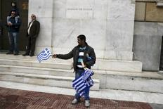 "A street vendor displays Greek national flags for sale in front of the Bank of Greece headquarters during a student parade marking the ""Ohi"" (No) day, the country's rejection on Italy's ultimatum to surrender as the World War II flared up, in Athens, Greece, October 28, 2015. REUTERS/Alkis Konstantinidis"