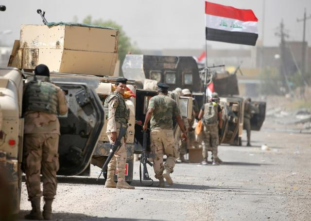 Iraqi army soldiers carry their weapons as they gather in the center of Falluja. REUTERS/Thaier Al-Sudani