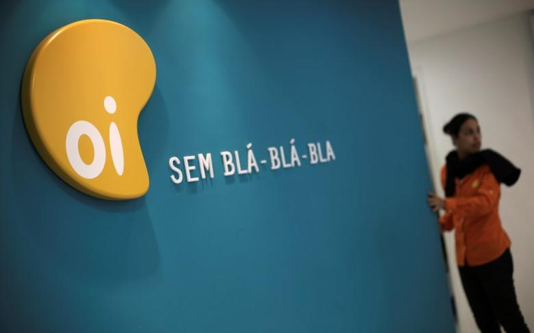 A woman stands next to the logo of Brazil's largest fixed-line telecoms group Oi, inside a shop in Sao Paulo October 2, 2013. REUTERS/Nacho Doce